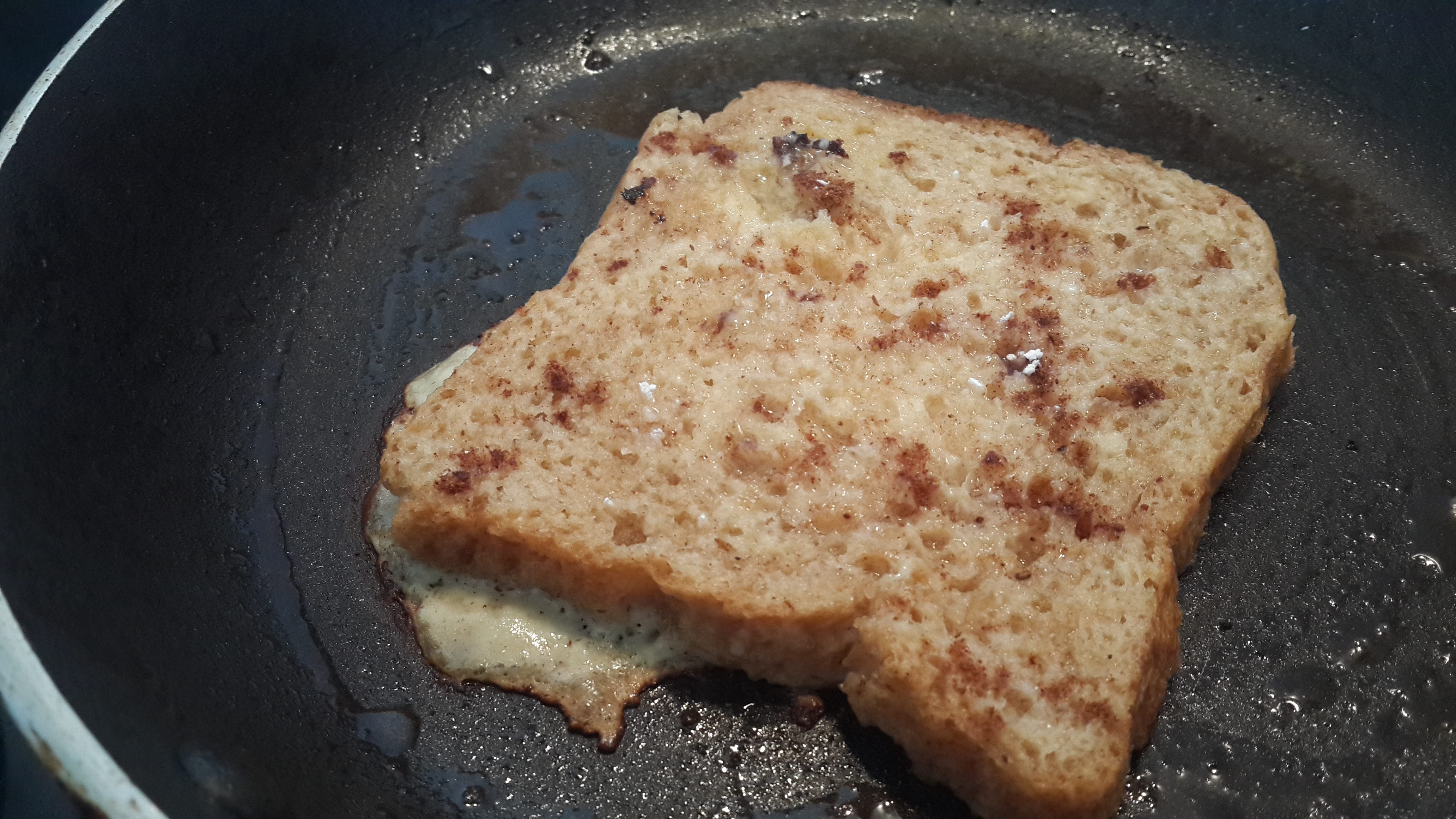 French toast sprinkled with cinnamon powder and caster sugar, in progress